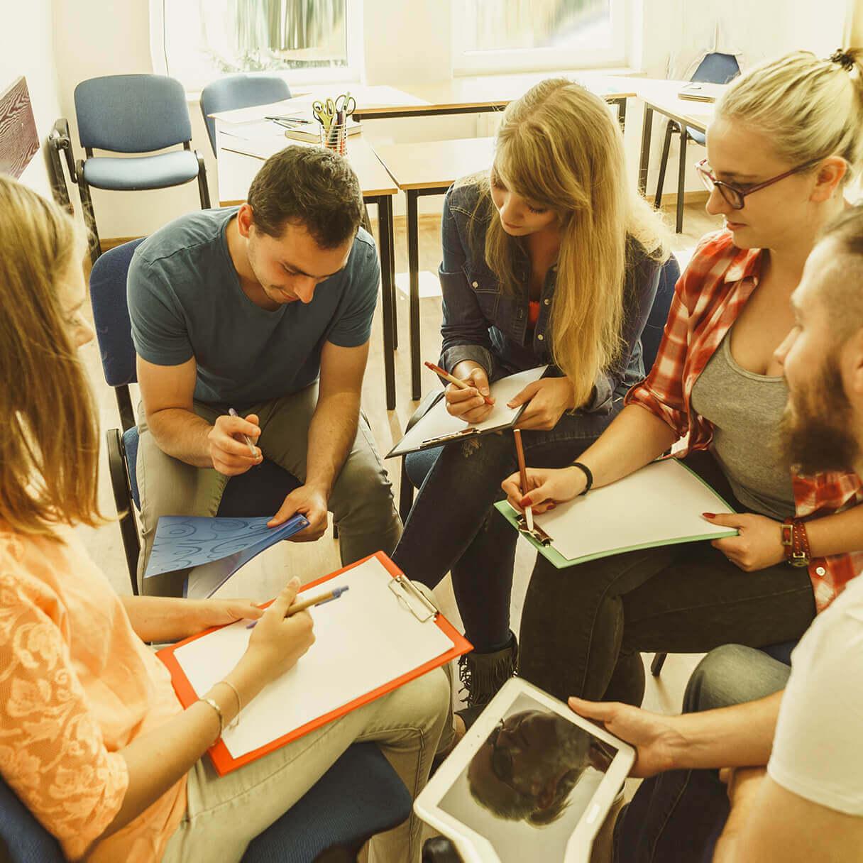 Grupo de estudantes sentados com prancheta nas mãos